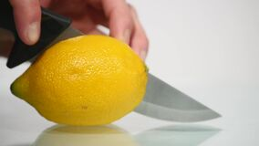 Το χέρι κόβει ένα λεμόνι με ένα μαχαίρι απόθεμα βίντεο