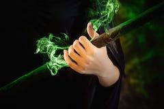το χέρι μαγισσών ` s κρατά ένα μαγικό προσωπικό στοκ εικόνα
