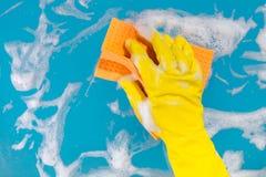 Το χέρι με ένα κουρέλι καθαρίζει την επιφάνεια Στοκ Εικόνα