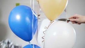 Το χέρι με ένα μαχαίρι διαπερνά τα μπαλόνια και φυσηκαν μακριά και εκρήγνυνται κίνηση αργή απόθεμα βίντεο