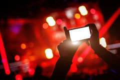 Το χέρι με ένα smartphone καταγράφει το φεστιβάλ ζωντανής μουσικής, ζωντανή συναυλία, παρουσιάζει στη σκηνή στοκ φωτογραφία με δικαίωμα ελεύθερης χρήσης