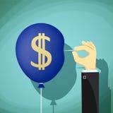 Το χέρι με τη βελόνα διαπερνά το μπαλόνι Σύμβολο νομίσματος δολαρίων ST Στοκ Εικόνες