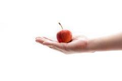Το χέρι με το μήλο απομονώνει στο υπόβαθρο μορίων Στοκ εικόνες με δικαίωμα ελεύθερης χρήσης