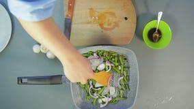 Το χέρι μιας γυναίκας ανακατώνει ένα κρεμμύδι ανακατώνω-τηγανητών και πράσινα φασόλια με ξύλινο spatula φιλμ μικρού μήκους