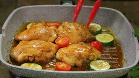 Το χέρι μιας γυναίκας γυρίζει τα κομμάτια των λαχανικών με τις λαβίδες και το κοτόπουλο επάνω σε ένα τηγάνι σχαρών και χύνει τη σ φιλμ μικρού μήκους