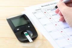Το χέρι μιας γυναίκας καταγράφει τα αποτελέσματα μέτρησης σε μια μορφή, για να ελέγξει το επίπεδο ζάχαρης στο υπομονετικό αίμα `  στοκ φωτογραφία