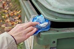 Το χέρι μιας ηλικιωμένης γυναίκας ρίχνει ένα τσαλακωμένο, βρώμικο πλαστικό BA Στοκ εικόνα με δικαίωμα ελεύθερης χρήσης