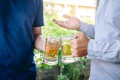 Το χέρι νεαρών άνδρων δύο αυξάνει ένα ποτήρι της μπύρας για να γιορτάσει την ευτυχή μπύρα κατανάλωσης φεστιβάλ διακοπών υπαίθρια  στοκ φωτογραφία με δικαίωμα ελεύθερης χρήσης