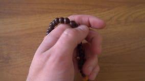 Το χέρι νεαρών άνδρων ` s αγγίζει rosary απόθεμα βίντεο