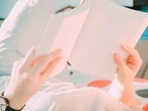 Το χέρι ομορφιάς από τη γυναίκα hipster που βρίσκεται στο κρεβάτι με τη λαβή και βλέπει Στοκ Εικόνες