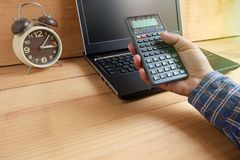 Το χέρι πίεσε τον επιστημονικό υπολογιστή με το lap-top στοκ εικόνα