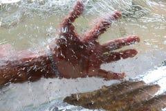 Το χέρι πίσω από την επιφάνεια πάγου Στοκ Φωτογραφίες