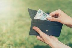 Το χέρι παίρνει έξω ένα τραπεζογραμμάτιο των ρωσικών ρουβλιών από ένα πορτοφόλι στοκ εικόνες