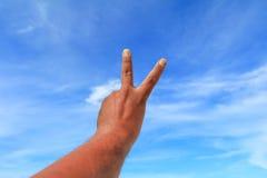 Το χέρι παρουσιάζει μετρώντας αριθμό δύο στο υπόβαθρο ουρανού Στοκ Εικόνες