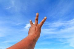 Το χέρι παρουσιάζει μετρώντας αριθμό τρία στο υπόβαθρο ουρανού Στοκ Εικόνες