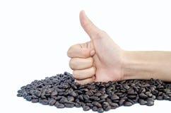 Το χέρι παρουσιάζει τους αντίχειρες και φασόλια καφέ στοκ φωτογραφία με δικαίωμα ελεύθερης χρήσης