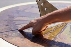 Το χέρι παρουσιάζει χρόνο στο αρχαίο ηλιακό ρολόι στοκ φωτογραφίες