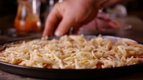 Το χέρι περιστρέφεται μια πίτσα που ψεκάζεται με το τυρί στο τηγάνι ψησίματος απόθεμα βίντεο