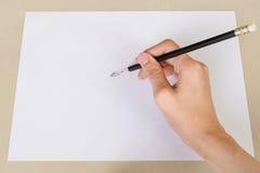 Το χέρι που γράφει από τη γόμα μολυβιών στη Λευκή Βίβλο και σβήνει το λάστιχο στο γραφείο Στοκ εικόνα με δικαίωμα ελεύθερης χρήσης