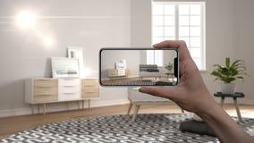 Το χέρι που κρατά το έξυπνο τηλέφωνο, εφαρμογή του AR, μιμείται τα έπιπλα και τα εσωτερικά προϊόντα σχεδίου στο πραγματικό σπίτι, ελεύθερη απεικόνιση δικαιώματος