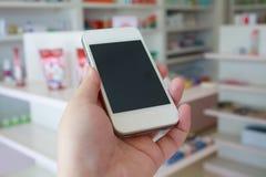 Το χέρι που κρατά το έξυπνο τηλέφωνο με τη θαμπάδα μερικοί τοποθετεί σε ράφι του φαρμάκου στοκ εικόνες