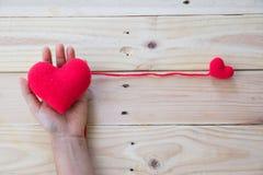 Το χέρι που κρατά το κόκκινο τσιγγελάκι καρδιών πλέκει του νήματος Στοκ φωτογραφία με δικαίωμα ελεύθερης χρήσης