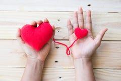 Το χέρι που κρατά το κόκκινο τσιγγελάκι καρδιών πλέκει του νήματος Στοκ Εικόνες