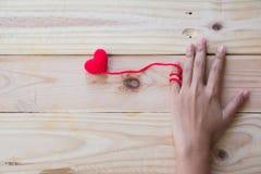 Το χέρι που κρατά το κόκκινο τσιγγελάκι καρδιών πλέκει Στοκ Εικόνες