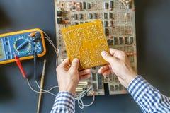Το χέρι που κρατά μια ηλεκτρική αποτύπωση επισκευής πινάκων κυκλωμάτων και συγκεντρώνει την έννοια φ ηλεκτρονικής στοκ φωτογραφίες με δικαίωμα ελεύθερης χρήσης