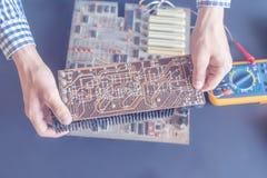 Το χέρι που κρατά μια ηλεκτρική αποτύπωση επισκευής πινάκων κυκλωμάτων και συγκεντρώνει την έννοια φ ηλεκτρονικής στοκ εικόνα