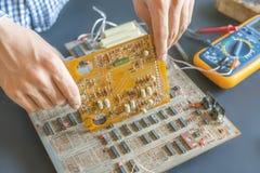 Το χέρι που κρατά μια ηλεκτρική αποτύπωση επισκευής πινάκων κυκλωμάτων και συγκεντρώνει την έννοια φ ηλεκτρονικής στοκ εικόνες με δικαίωμα ελεύθερης χρήσης