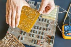 Το χέρι που κρατά μια ηλεκτρική αποτύπωση επισκευής πινάκων κυκλωμάτων και συγκεντρώνει την έννοια φ ηλεκτρονικής στοκ φωτογραφία