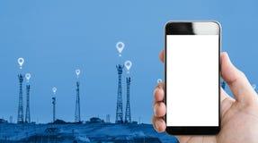 Το χέρι που κρατούν την κινητή τηλεφωνική άσπρη οθόνη, οι πύργοι τηλεπικοινωνιών και τα εικονίδια θέσης υπογράφουν το υπόβαθρο στοκ φωτογραφίες με δικαίωμα ελεύθερης χρήσης