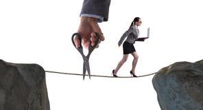 Το χέρι που κόβει το σχοινί κάτω από τον περιπατητή σχοινιών σχοινοβασίας επιχειρηματιών Στοκ Φωτογραφία
