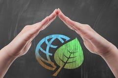 Το χέρι που προστατεύει τη γήινη σφαίρα με το πράσινο φύλλο επισύρει την προσοχή στον πίνακα Στοκ Εικόνες