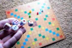 Το χέρι που ρίχνει το λευκό χωρίζει σε τετράγωνα το ζωηρόχρωμο θολωμένο επιτραπέζιο παιχνίδι υποβάθρου Η δυναμική στιγμή του παιχ Στοκ Φωτογραφία