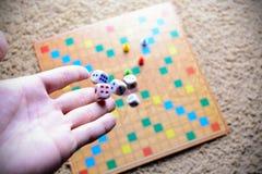 Το χέρι που ρίχνει το λευκό χωρίζει σε τετράγωνα το ζωηρόχρωμο θολωμένο επιτραπέζιο παιχνίδι υποβάθρου Η δυναμική στιγμή του παιχ Στοκ εικόνες με δικαίωμα ελεύθερης χρήσης