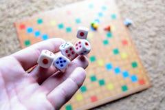 Το χέρι που ρίχνει το λευκό χωρίζει σε τετράγωνα το ζωηρόχρωμο θολωμένο επιτραπέζιο παιχνίδι υποβάθρου Η δυναμική στιγμή του παιχ Στοκ φωτογραφία με δικαίωμα ελεύθερης χρήσης