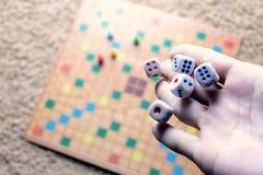 Το χέρι που ρίχνει το λευκό χωρίζει σε τετράγωνα το ζωηρόχρωμο θολωμένο επιτραπέζιο παιχνίδι υποβάθρου Η δυναμική στιγμή του παιχ Στοκ φωτογραφίες με δικαίωμα ελεύθερης χρήσης