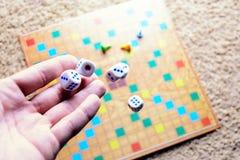 Το χέρι που ρίχνει το λευκό χωρίζει σε τετράγωνα το ζωηρόχρωμο θολωμένο επιτραπέζιο παιχνίδι υποβάθρου Η δυναμική στιγμή του παιχ Στοκ εικόνα με δικαίωμα ελεύθερης χρήσης