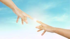 Το χέρι που φθάνει στο δάχτυλο μαζί με λάμπει φωτεινό φως, στο υπόβαθρο ουρανού στοκ εικόνα με δικαίωμα ελεύθερης χρήσης