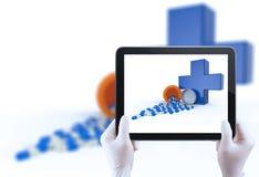 Το χέρι που χρησιμοποιεί τον υπολογιστή ταμπλετών παρουσιάζει χάπια που ανατρέπουν από το χάπι bottl Στοκ Εικόνες