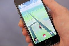 Το χέρι προσώπων που παίζει Pokemon πηγαίνει εφαρμογή στο iPhone μήλων Στοκ φωτογραφία με δικαίωμα ελεύθερης χρήσης