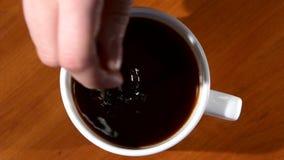 Το χέρι προσώπων ` s ανακατώνει τη ζάχαρη στο φλυτζάνι του μαύρου καφέ απόθεμα βίντεο