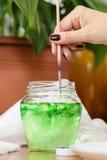 Το χέρι πλένει το πράσινο χρώμα από τη βούρτσα στο βάζο γυαλιού Στοκ Φωτογραφίες