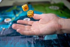 Το χέρι ρίχνει δύο κίτρινα χωρίζει σε τετράγωνα στο αγωνιστικό χώρο Τύχη και ενθουσιασμός Επιτραπέζια παιχνίδια Στιγμές τυχερού π στοκ φωτογραφίες με δικαίωμα ελεύθερης χρήσης