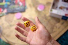 Το χέρι ρίχνει δύο κίτρινα χωρίζει σε τετράγωνα στο αγωνιστικό χώρο Τύχη και ενθουσιασμός Επιτραπέζια παιχνίδια Στιγμές τυχερού π στοκ φωτογραφία