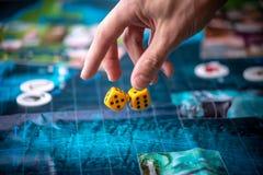 Το χέρι ρίχνει δύο κίτρινα χωρίζει σε τετράγωνα στο αγωνιστικό χώρο E Τύχη και ενθουσιασμός Στρατηγική επιτραπέζιων παιχνιδιών στοκ φωτογραφία