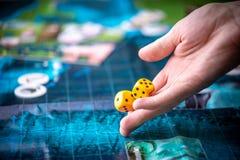 Το χέρι ρίχνει δύο κίτρινα χωρίζει σε τετράγωνα στο αγωνιστικό χώρο Στιγμές τυχερού παιχνιδιού στη δυναμική Τύχη και ενθουσιασμός στοκ φωτογραφία με δικαίωμα ελεύθερης χρήσης