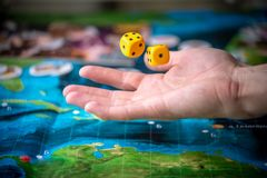 Το χέρι ρίχνει δύο κίτρινα χωρίζει σε τετράγωνα στο αγωνιστικό χώρο Στιγμές τυχερού παιχνιδιού στη δυναμική Τύχη και ενθουσιασμός στοκ εικόνα με δικαίωμα ελεύθερης χρήσης
